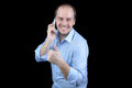 Man smiling talking mobile phone with thumbs up blue shirt Royalty Free Stock Photography