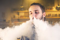 The man smoke an electronic cigarette at the vape shop. close-up. Royalty Free Stock Photo