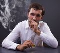 Man smoking a cigar young businessman enjoying glass of whiskey in his office portrait of young Stock Image