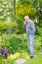 Man sneezing hay fever senior old with in his garden Stock Photography