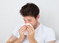 Man sneezing into a tissue young blowing his nose in white paper Royalty Free Stock Images