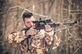 Man with a sniper and shooting on an open season, looking through scope Royalty Free Stock Photo
