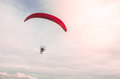 A man soaring into the sky with paramotor extreme sport adventure in summer day time with a clear sky background. Royalty Free Stock Photo