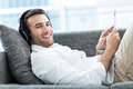 Man on sofa with digital tablet headphones and Stock Photo