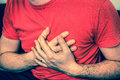 Man on sofa having chest pain, heart attack