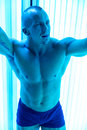 Man in solarium young muscular at beauty salon Royalty Free Stock Photography