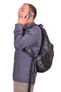 Man is speaking on mobile phone young attractive guy with backpack his cellphone white background Stock Photo