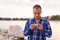 Man spending time on seashore and using phone Stock Photo