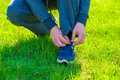 Man in a sports suit to tie his shoes on the lawn Royalty Free Stock Photos