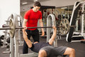 Man spotting his friend on a bench press athletic young men while he lifts some weights at gym Royalty Free Stock Photos