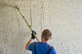 Man spraying concrete stucco to wall worker using a sprayer tool apply a large Royalty Free Stock Images