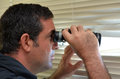 Man spy age looks and searches with binoculars and looks out through venetian blinds concept photo of curious nosy Royalty Free Stock Image