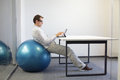 Man on stability ball at desk relaxed position young working with tablet Royalty Free Stock Images