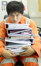 Man in stacks of paperwork working room Stock Images