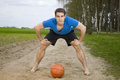 Man stand over the ball frontal wide angle shooting of a young in a blue t shirt short black shorts and barefoot in low posture Royalty Free Stock Photos