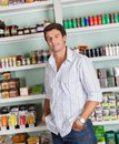 Man standing against shelves in store portrait of handsome mid adult with hands pockets at grocery Royalty Free Stock Images