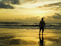 Man standing alone beach looking ocean sunrise come Royalty Free Stock Photo