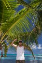 Man standing beneath palm tree on tropical beach young holding to fronds Royalty Free Stock Photo