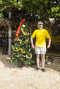 Man standing besides a christmas tree on a beach pretending to be santa claus by caribbean Royalty Free Stock Image