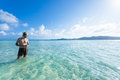 Man standing in clear tropical beach water okinawa japan with snorkel enjoying crystal of a kume island Stock Photos