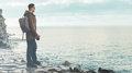 Man standing on coastline with photo camera Royalty Free Stock Photo