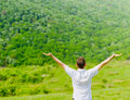 Man standing on a field with arms wide open enjoying Stock Photos