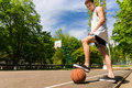 Man standing with foot on basketball on court low angle view of young athletic side lines of top of ball preventing it from Stock Photography