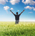 Man standing on the green field under sky Royalty Free Stock Photo