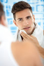 Man standing in his bathroom after shaving in the morning young cleaning face with a towel Stock Images