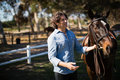 Man standing with horse in the ranch Royalty Free Stock Photo