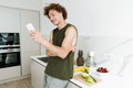 Man standing at the kitchen and chatting by phone Royalty Free Stock Photo