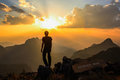 Man standing on mountain peak at sunset Royalty Free Stock Photo