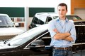 Man standing near a car with his arms crossed showroom Royalty Free Stock Images