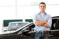 Man standing near a car with his arms crossed showroom Stock Photography