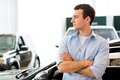 Man standing near a car with his arms crossed showroom Royalty Free Stock Photography