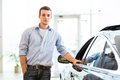 Man standing near a car young in showroom put his hand on the door Royalty Free Stock Photo