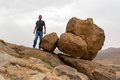 Man standing near rolling round big rocks on the edge of a mountain