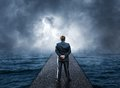 Man standing on pier looks at the sea Royalty Free Stock Photo