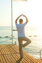 Man standing on a pier on one leg and holds the balance Royalty Free Stock Images