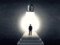 Man standing on a step in front of a huge light bulb Royalty Free Stock Photo