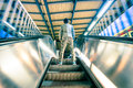 Man standing on treadmills escalator stairway with soft motion Royalty Free Stock Photo