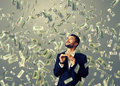 Man standing under dollar s rain excited laughing businessman holding money and looking up Stock Image