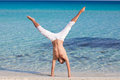 A man is standing upside down on the beach Royalty Free Stock Photos