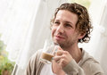 Man standing by a window drinking coffee portrait of handsome young sips Royalty Free Stock Photo