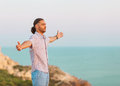 Man stands on a cliff near the sea at sunset Stock Photos