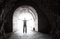 Man stands in dark tunnel with glowing end the Royalty Free Stock Photos
