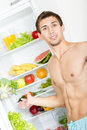 Man stands near the opened fridge with fruit which is full of and vegetables Stock Photography