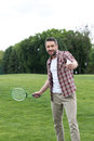 Man sticking tongue out during play badminton game in park, summertime concept Royalty Free Stock Photo