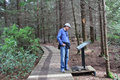 Man Stops to Read the Sign while Hiking Royalty Free Stock Photo