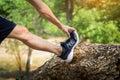 Man stretching leg as warm-up before run